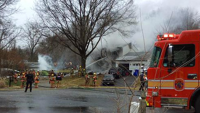 Rauch steigt über Haus auf. Daneben Feuerwehrauto.