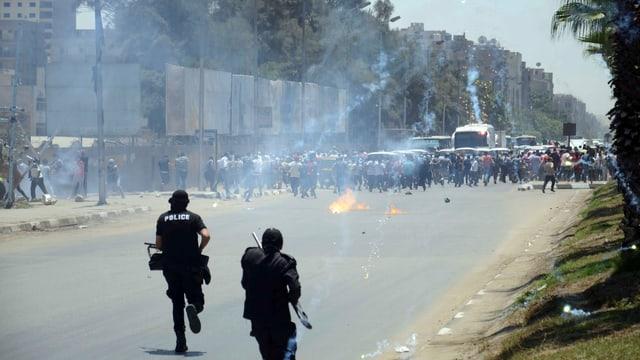 Bewaffnete Sicherheitskräfte rennen Demonstranten hinterher.