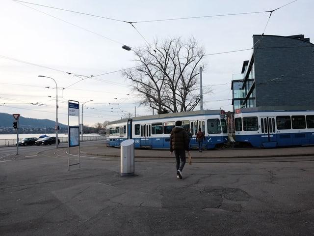Ein blau-weisses Tram steht an der Endstation, links im Bild der See.