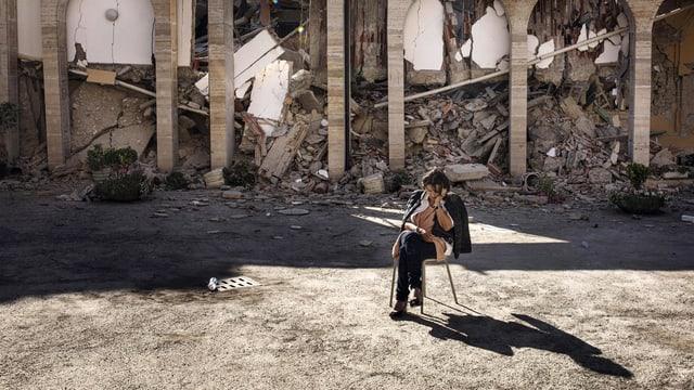 Ein Frau sitzt trauernd vor ihrem zerstörten Haus.
