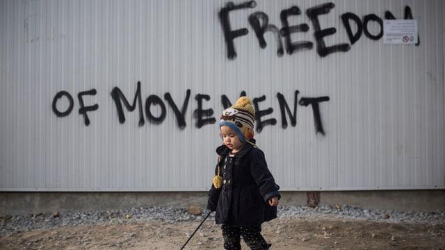 Ein Kleinkind vor einer Wand mit der Aufschrift «Freedom of movement»