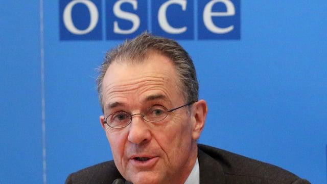 Ein Mann mit Brille vor dem OSCE-Emblem