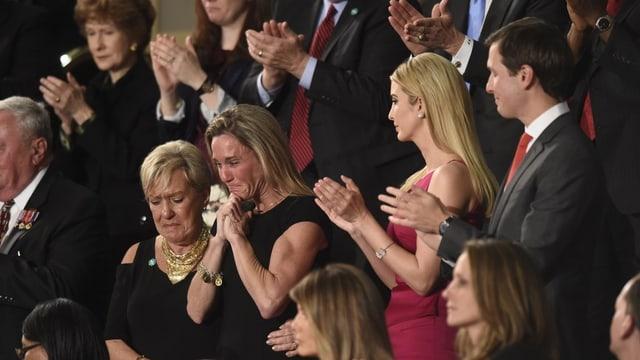 Eine Frau weint in einer Menschenmenge. Die Leute um sie stehen und klatschen.