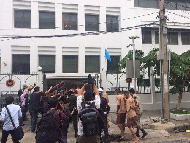 Journalisten stürzen sich auf Gefangene, die beim Militärgericht in Bangkok ankommen.