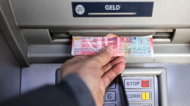 Jemand nimmt Geld aus einem Bankomaten.