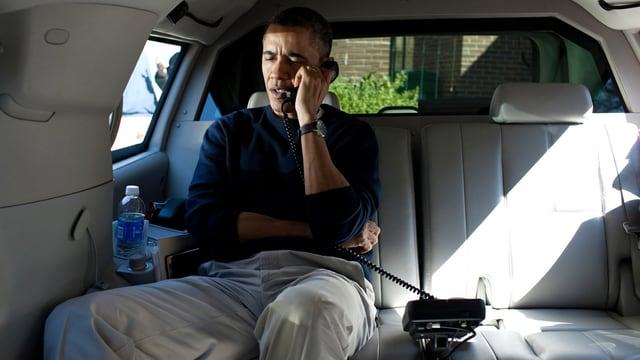 Barack Obama telefoniert auf dem Rücksitz eines geräumigen Wagens.