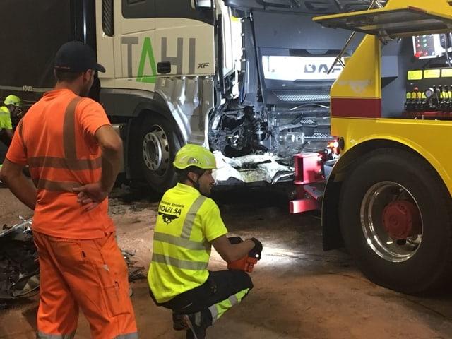 Demolierter LKW wird von zwei Männern begutachtet.