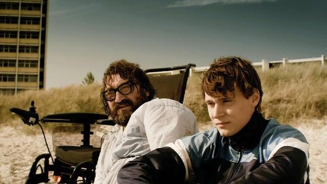 Ein Mann mit Brille sitzt neben seinem Rollstuhl im Sand, daneben sitzt ein Junge.