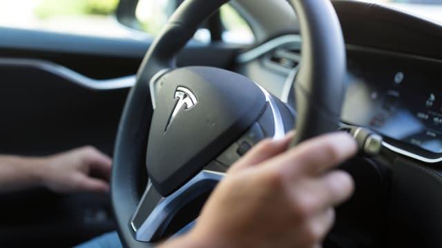 Logo Tesla vid la roda da l'auto.
