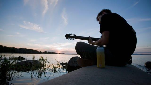 Ein Mann sitzt mit der Gitarre und einem kühlen Getränk am See.