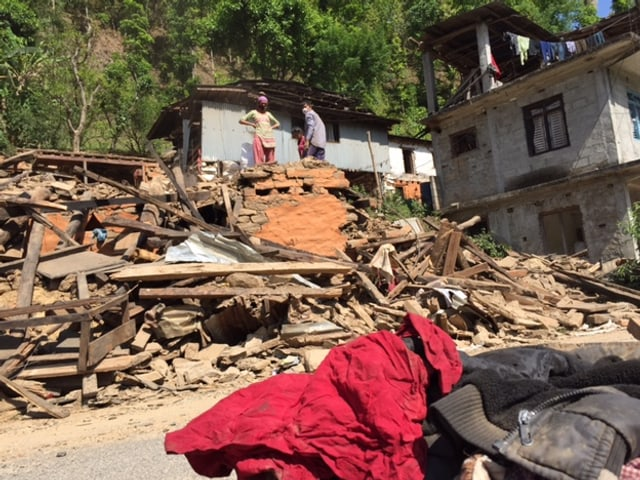 Zwei Männer stehen auf den Trümmern eines Hauses.