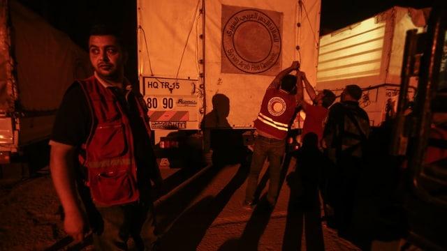 Helfer in Syrien entladen einen Lastwagen mit Hilfsgütern.