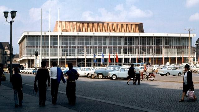 Historische Aufnahme eines grossen rechteckigen Gebäudes, vor dem zahlreiche Autos stehen.