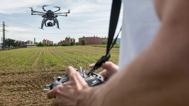Ein Mann steuert eine Drohne, die eine Spiegelreflexkamera tragen kann, über freiem Feld.