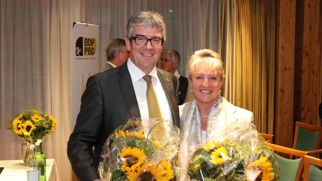 Jon Domenic Parolini links und Barbara Janom Steiner rechts lachen mit Blumen in die Kamera.