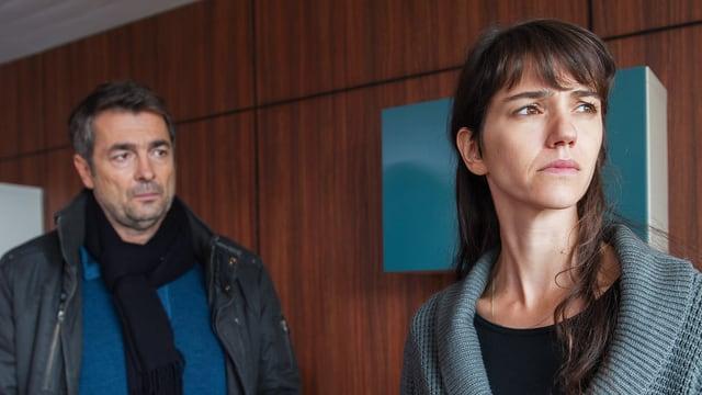 Eine Frau steht mit ernstem Gesicht neben einem Mann. Sie hat den Blick von ihm abgewendet.