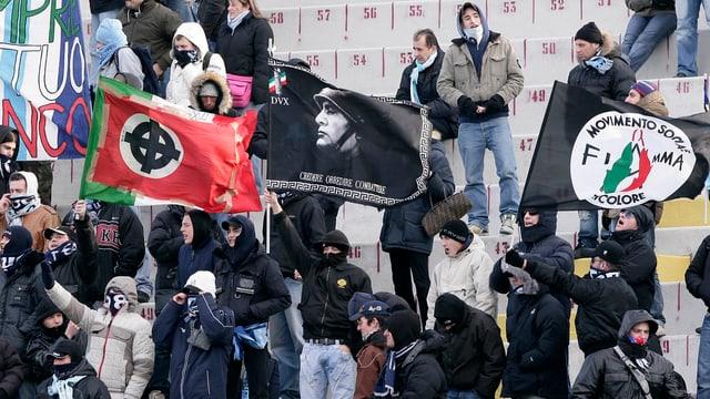 Schwarz vermummte Männer auf einer Stadiontribüne.