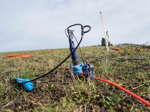 Ein Teil aus hell- und dunkelblauen Plastikteilen steckt in einer Wiese, orange und schwarze Kabel führen in verscheidene Richtungen.