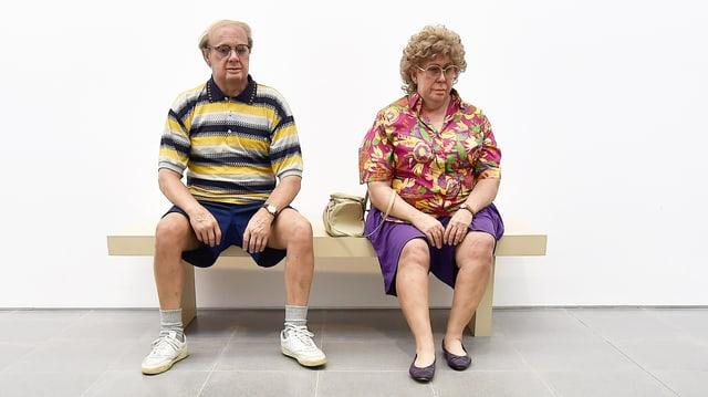 Eine Skulptur: ein älteres Ehepaar sitzt nebeinander auf einer Bank, starren beide in die Leere.