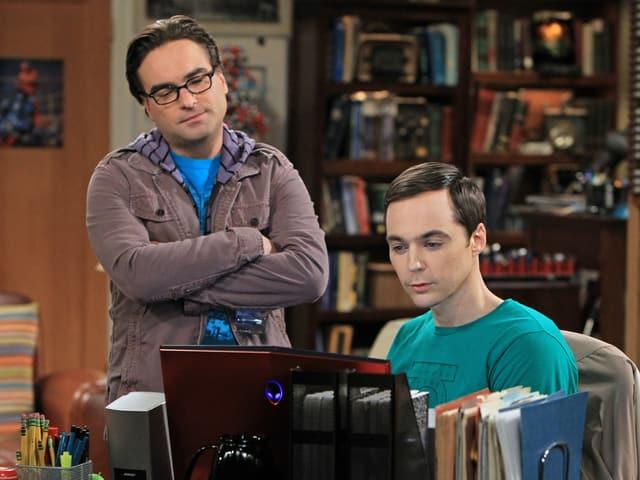 Szene aus der TV-Serie: Zwei Männer schauen auf einen Laptop.