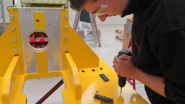 Ein Arbeiter bohrt auf einer gelben Fläche.