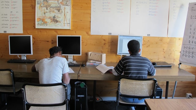 Zwei minderjährige Asylsuchende sitzen an einem Tisch.