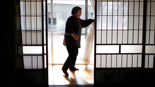 Eine japanische Frau zieht Vorhänge zur Seite