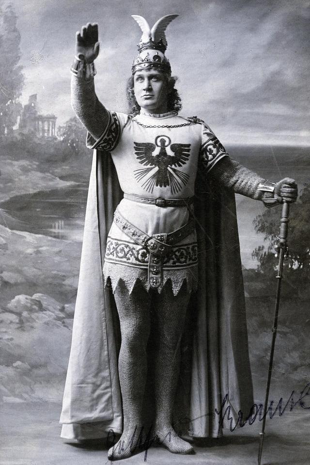 Mann mit Adler auf dem Kostüm und erhobenem Arm.