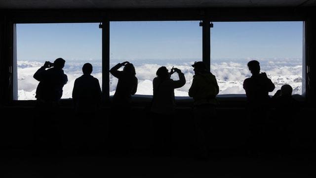 Menschen stehen vor einem Fenster auf dem Jungfraujoch.