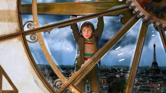 Ein Junge hängt an einer riesigen Uhr, im Hintergrund ist der Eiffelturm zu sehen.