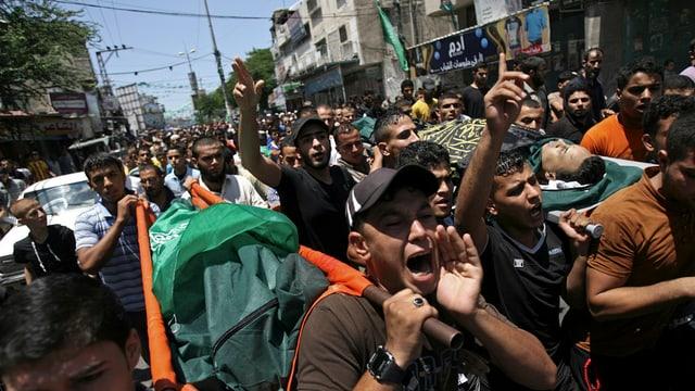 Palästinenser ziehen demonstrierend durch eine Strasse in Gaza.