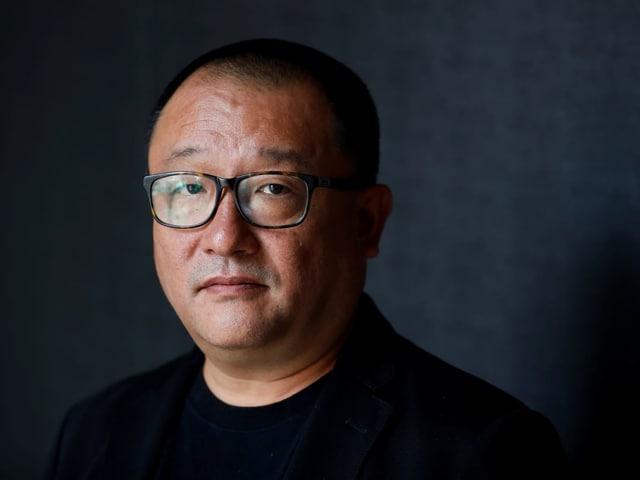 Nahaufnahme: Ein Mann mit asiatischer Herkunft schaut in die Kamera. Er hat kurze, schwarze Haare, trägt eine schwarze Hornbrille, ein schwarzes T-Shirt und darüber ein dunkles, samitges Jakett.
