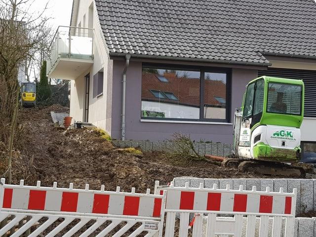 Umgegrabener Garten vor einem Haus mit Absperrungen.