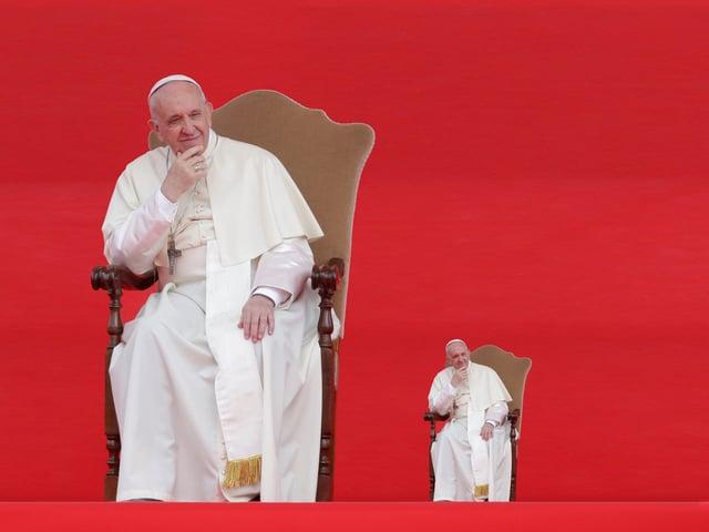 Papst Franziskus sitzt auf einem Stuhl, einmal in Gross, einmal in Klein.