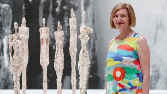 Eine Frau steht vor vier Giacometti-Skulpturen.