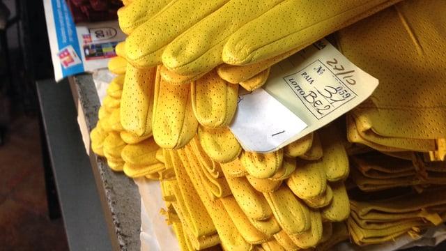 Mehrere Paare gelber Lederhandschuhe liegen auf einem Stapel.
