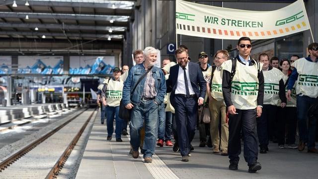 Umens chaminan tras ina staziun da tren cun ina bandiera Wir Streiken