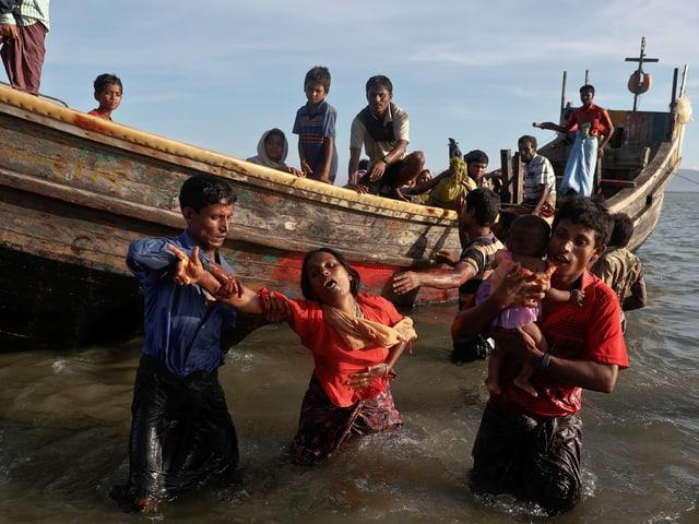 Rohingya-Flüchtlinge steigen an der Küste von Bangladesch aus einem Boot.