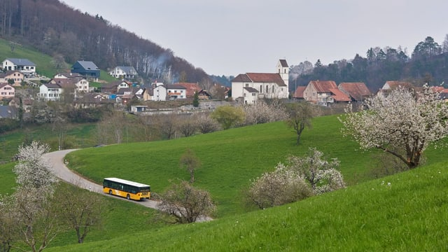 Aufnahme Dorf, Postauto fährt auf schmaler Strasse zu den Häusern