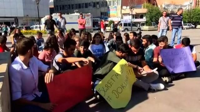 Protestierende Schüler mit Transparenten sitzen am Boden.