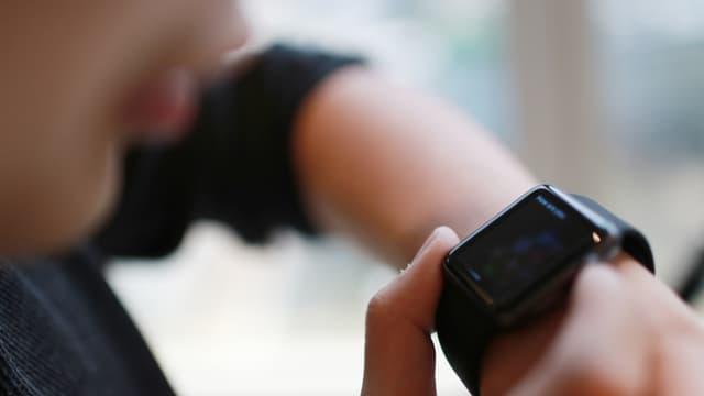 Ein Junge spricht in seine Smartwatch.