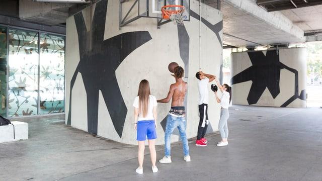 Vier Jugendliche stehen vor einem Basketball-Korb.