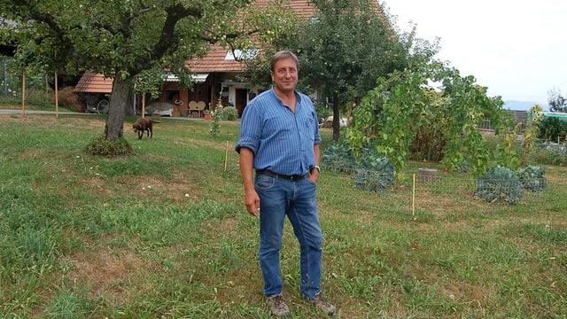 Ein Mann steht auf einer Wiese vor einem Bauernhof.