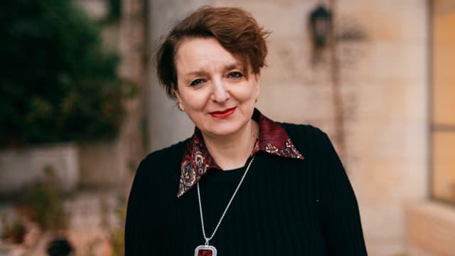 Eine Frau mit schwarzem Pullover vor einer Hausfassade. Sie schaut in die Kamera.