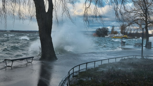 Wellen des Zugersees schlagen über die Uferpromenade.