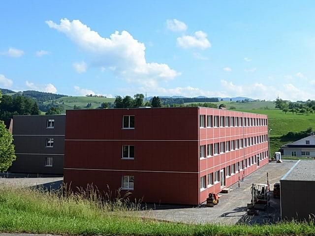 Ein rotes Gebäude und ein graues Gebäude.