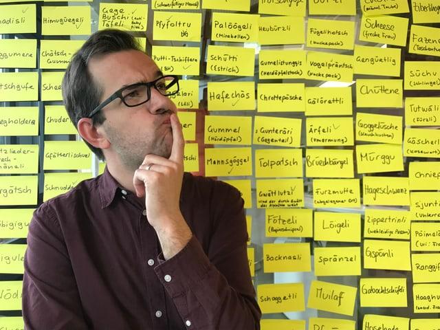 Mann vor einer Wand mit gelben Zetteli.