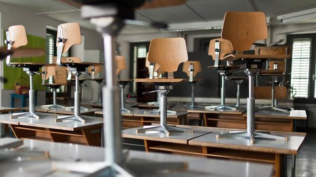 Auf den Pult gestellte Stühle in einem Klassenzimmer