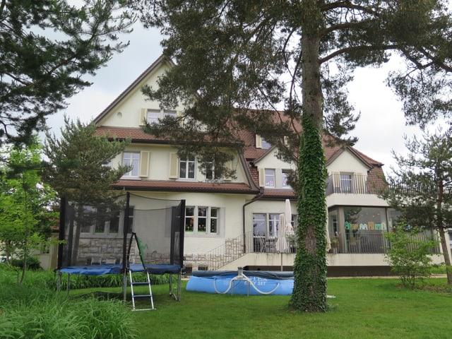 Haus hinter Baum.