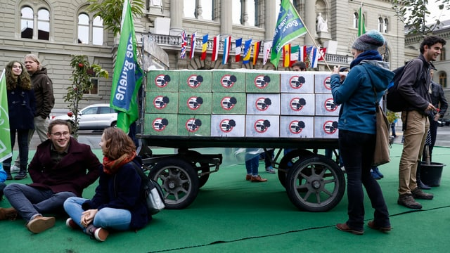 Wagen mit Unterschriftenpaketen, daneben junge Initianten